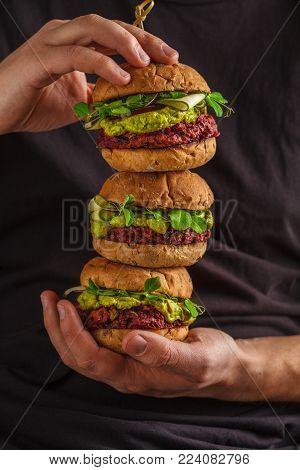Vegan healthy burgers in man's hands. Vegan beet chickpea burgers with vegetables, guacamole and rye buns. Healthy vegan food concept.