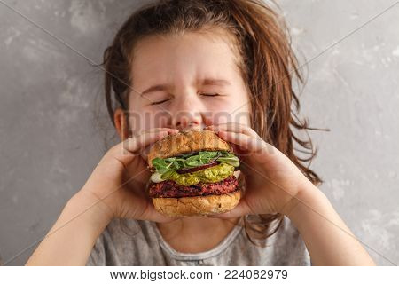 Beautiful happy hungry baby girl eating vegan burger.  Vegan beet chickpea burgers with vegetables, guacamole and rye buns. Healthy child vegan food concept.