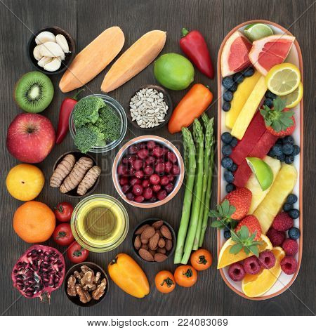 Health food for heart fitness concept with superfoods of fresh fruit, vegetables, seeds, nuts, herbs and spice  providing high levels of omega 3 fatty acids, vitamins, anthocyanins and antioxidants.