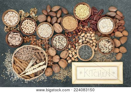 Dried high fibre health food concept with whole wheat pasta, grains, cereals, legumes, nuts and seeds with  rustic kitchen sign. Foods high in omega 3 fatty acids, antioxidants and vitamins.