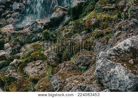 Mossy stone rock with river at background, selective focus, toned