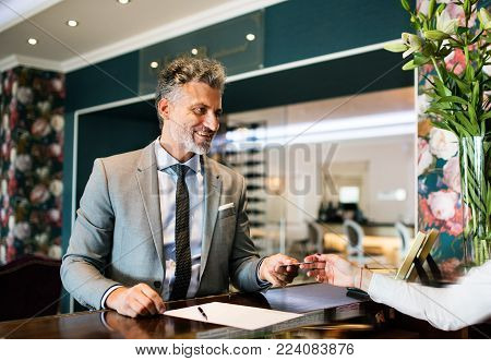 Mature businessman checking in at hotel reception.
