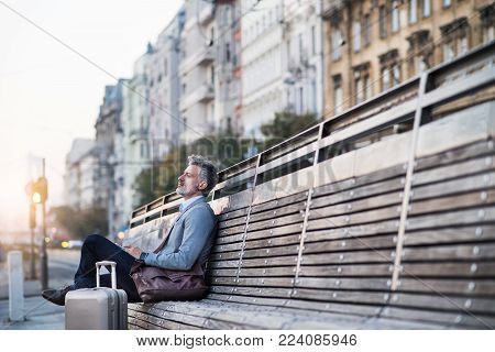 Handsome mature businessman in a city, sitting on a bench, waiting.