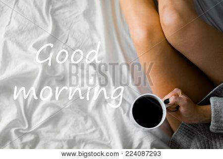 Closeup Beautiful Girl in warm knitted Morning Socks. Woman Reading Book and Drinking a Drink in the Bedroom. Woman in Bed Reading a Book, early Winter Morning. Woman at sunrise, Rising Sun on Bed
