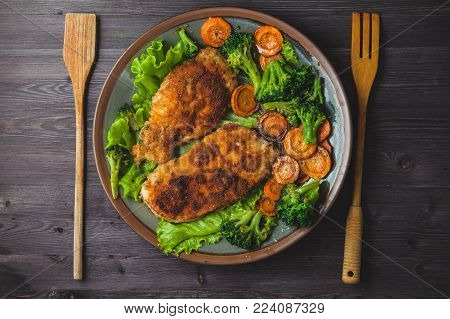 Chicken steak in breadcrumbs with vegetables on a plate. Menu, restaurant concept. Served in