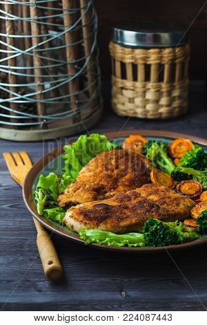 Chicken steak in breadcrumbs with vegetables on a plate. Menu, restaurant concept.