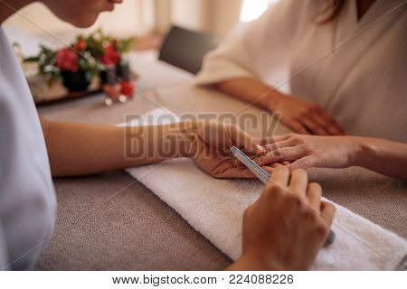 Hands of qualified manicurist filing the nails of woman client with a white buffer in nail salon. Focus on hands of manicurist shaping nails of female client in salon.