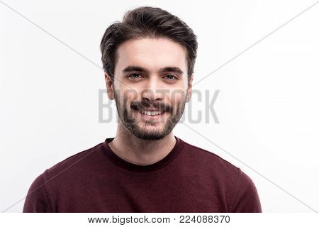 Epitome of masculinity. The portrait of a handsome dark-haired bristled young man in a burgundy sweater smiling at the camera while posing against a white background