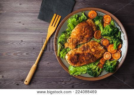 Chicken steak in breadcrumbs with vegetables on a plate. Menu, restaurant concept. Served in. Top view