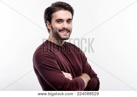 Very masculine. Cheerful handsome man standing half-turned and folding his arms across his chest while posing against a white background