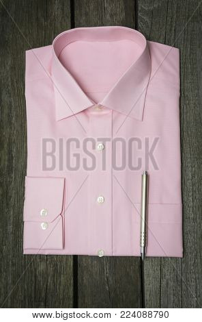 Pink Shirt And Pen On Wooden Background.