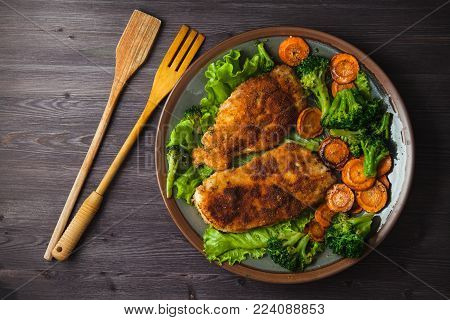 Chicken steak in breadcrumbs with vegetables on a plate. Menu, restaurant concept. Served in. Top view.
