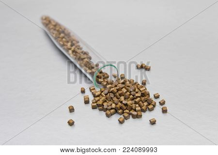 Plastic pallets . Colorant for polymers in granules. Golden mother of pearl granules of raw plastic for industry spilled out of the tube