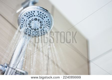 shower head with drops of water falling down