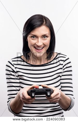 Avid player. Upbeat young woman playing video games, using a game controller, while standing isolated on a white background