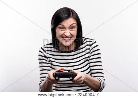 Avid gamer. Upbeat dark-haired young woman in a striped pullover playing video game and being excited about it while standing isolated on the white background