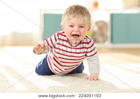 Front view portrait of a joyful baby crawling towards camera on the floor at home