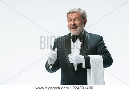 The smiling senior waiter holding white towel and standing isolated on white studio background