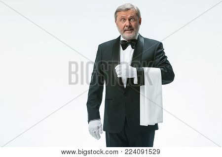 The surprised senior waiter holding white towel and standing isolated on white studio background
