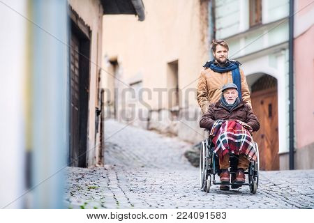Father in wheelchair and young son on a walk. A carer assisting disabled senior man.