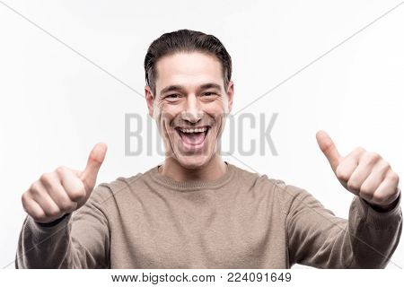 Everything is perfect. Upbeat young man showing thumbs up and grinning while being isolated on the white background