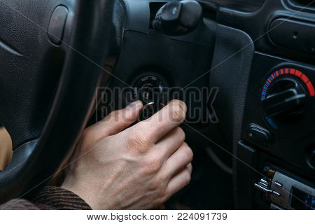 Closeup of male driver hand inserts key in ignition lock to start car