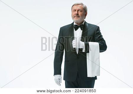 Senior waiter holding white towel and standing isolated on white studio background