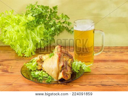 Baked ham hock on a dark glass dish and large glass mug with a handle of lager beer on an old rustic wooden table on background of greens and canvas