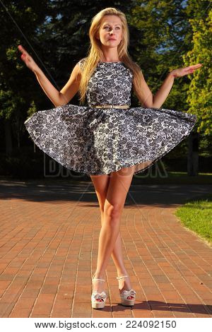Full length fashionable young woman in summer flowery dress outdoor relaxing in park stylized like marionette