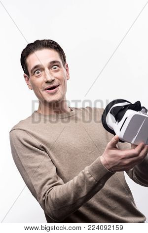 Unusual experience. Handsome young man looking into the camera with his eyes widened, having just tested virtual reality headset for the first time
