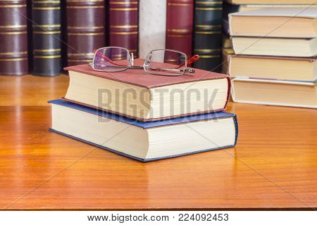 Classic mens eyeglasses lying on the stack of  two closed book in hardcover on a wooden table closeup against of the other books at selective focus