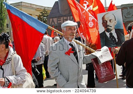 Volgograd, Russia - May 1, 2017: Old man with russian flag and newspapers takes part in the May day demonstration in Volgograd