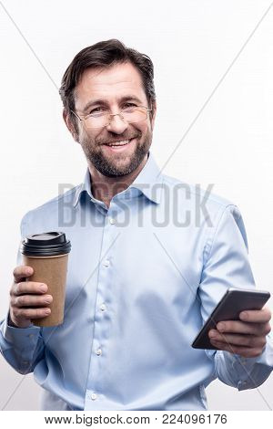 Replenishing energy. Handsome cheerful businessman posing for the camera and smiling brightly while holding a cup of coffee in one hand and a phone in the other one