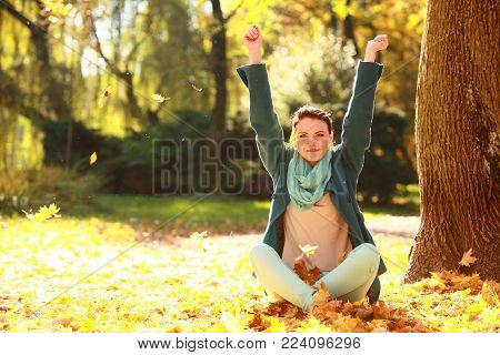 Happiness carefree. Young pretty woman relaxing in the autumn park throwing leaves up in the air with arms raised up, smiling elated expression. Beautiful girl in colorful forest foliage outdoor.