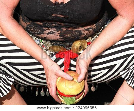 Street performing belly dancer having a hunch break eating a hamburger while sitting on the street.