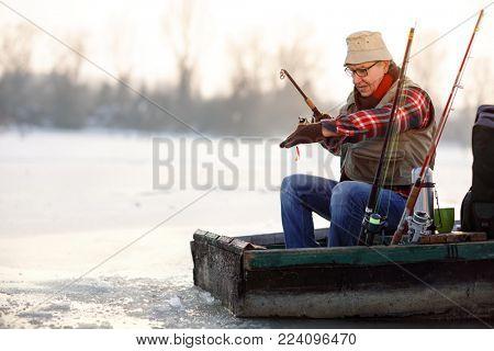 Old fisherman fishing on lake with bait