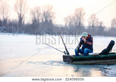 Old man fishing fish on winter and drinking tea in boat