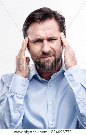 Severe headache. Handsome bearded middle-aged man pressing his fingers to his temples and wincing while suffering from migraine