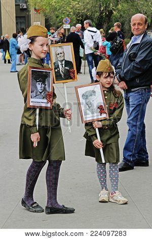 Volgograd, Russia - May 09, 2017: Girls in military uniform hold portraits of their relatives in the action