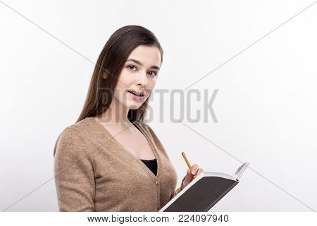 Creative poet. Charming young woman standing half-turned and writing poems in her notebook while posing for the camera