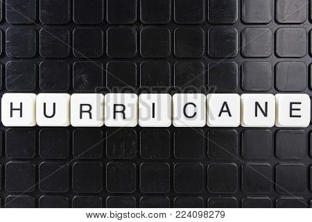 Hurricane text word title caption label cover backdrop background. Alphabet letter toy blocks on black reflective background. Hurricane.