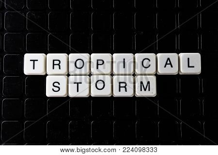 Tropical storm white text word on black cover. Text word crossword. Alphabet letter blocks game texture background. Storm.