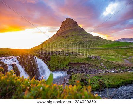 Sunset over landscape of Kirkjufell Mountain and Kirkjufell Waterfalls in summer Iceland