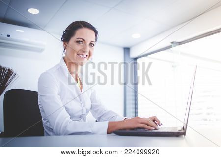 Beautiful Brunette Business Woman Standing In A Boardroom Working On A Tablet Computer