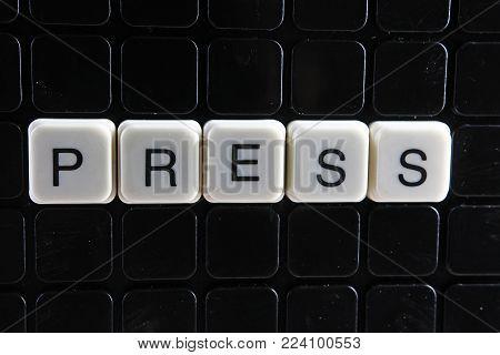 PRESS control text word title caption label cover backdrop background. Alphabet letter toy blocks on black reflective background. Press.