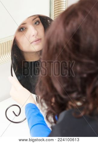 Curly brunette young woman looking at reflection of mirror by hairstylist hairdresser. In hairdressing salon.