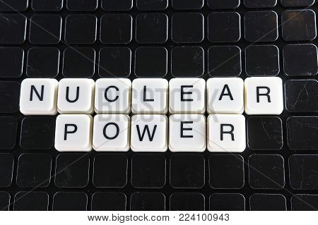 Nuclear power control text word title caption label cover backdrop background. Alphabet letter toy blocks on black reflective background. Nuclear power..