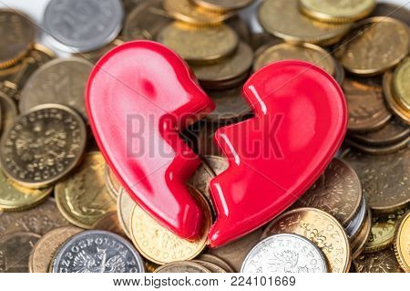 Broken red Valentines Day heart on a pile of coins. Love and money problems abstract concept.