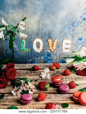 strawberries, macarons, flowers and love cookies on shabby background, valentines day concept