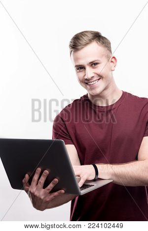 Enjoying work. Upbeat young man in a burgundy t-shirt holding a laptop and posing with it while standing isolated on a white background